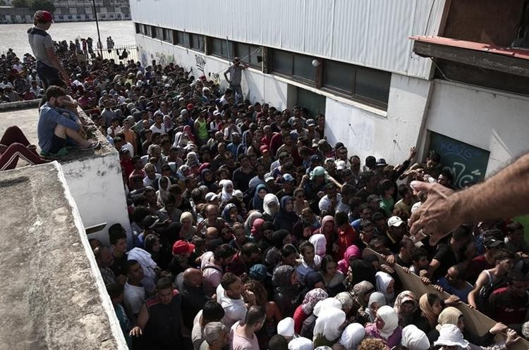 Hundreds of migrants gather for a registration procedure at the stadium of Kos town, on the southeastern island of Kos, Greece, Tuesday, Aug. 11, 2015. Fights broke out among migrants on the Greek island of Kos Tuesday, where overwhelmed authorities are struggling to contain increasing numbers of people arriving clandestinely on rubber dinghies from the nearby Turkish shore.  (AP Photo/Yorgos Karahalis)
