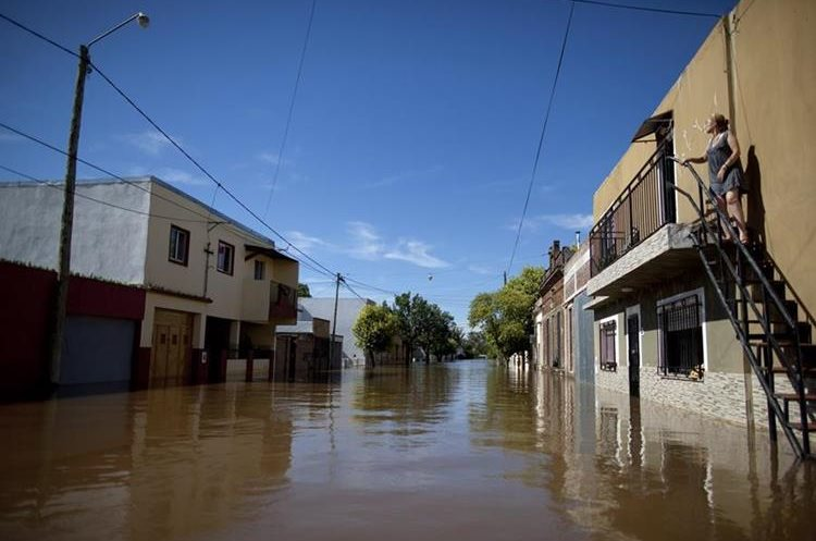 Alicia Fasana stands above floodwater outside her home in Concordia, Argentina, Monday, Dec. 28, 2015. The flooding, caused by heavy rains and bulging rivers, come at the beginning of the Southern Hemisphere