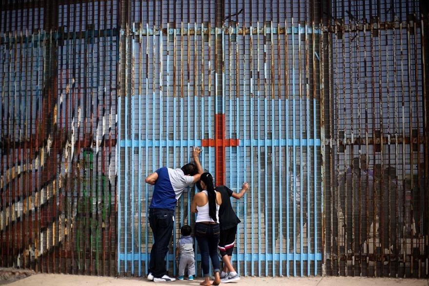 Integrantes de una familia en el lado mexicano de la frontera hablan con sus parientes en EE. UU. (Foto Prensa Libre: AFP).