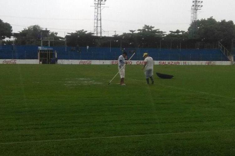 Trabajadores del estadio observan el estado de la cancha.