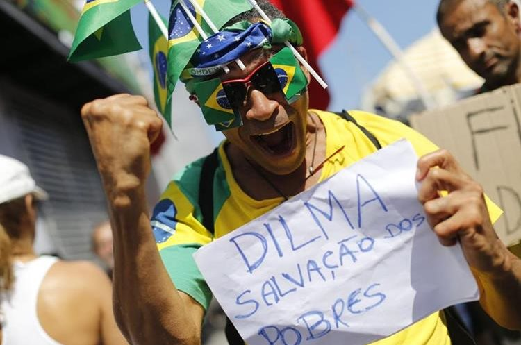 """A man holds a sign that reads in Portuguese """"Dilma is the salvation of the poor"""" during a protest against the impeachment of Brazil"""