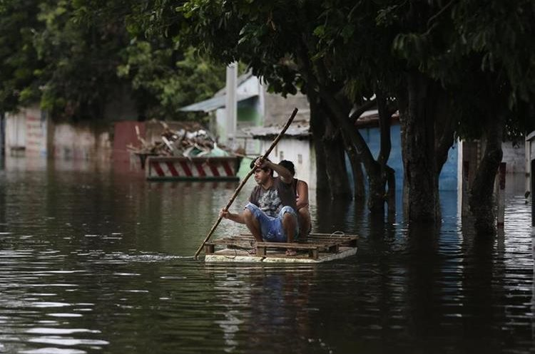 A couple drive a makeshift raft on a flooded street of Banado Noerte neighborhood in Asuncion, Paraguay, Sunday, Dec. 27, 2015. Widespread floods have forced nearly 140,000 people from their homes in Paraguay, Argentina, Uruguay and Brazil following days of torrential rains that drenched a region where the countries border each other. (AP Photo/Jorge Saenz)