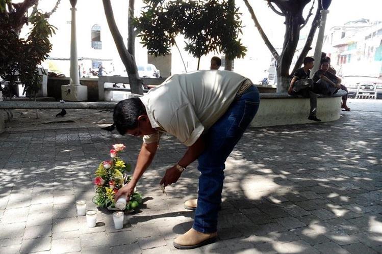 Vecino enciende veladoras en el parque central de Mazatenango, donde hace un año ocurrió el ataque contra dos periodistas. (Foto Prensa Libre)