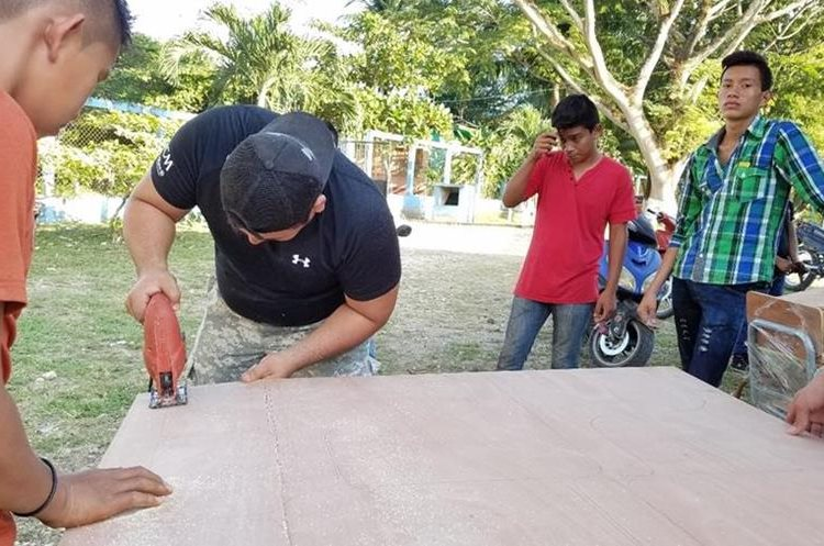 Estudiantes, maestros y padres de familia unieron esfuerzos para restaurar los pupitres. (Foto Prensa Libre: Rigoberto Escobar)