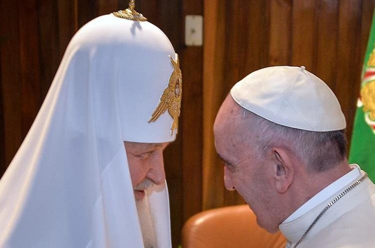 Pope Francis (R) and the head of the Russian Orthodox Church, Patriarch Kirill, greet each other during a historic meeting in Havana on February 12, 2016. Pope Francis and Russian Orthodox Patriarch Kirill kissed each other and sat down together Friday for the first meeting between their two branches of the church in nearly a thousand years. Francis, 79, in white robes and a skullcap and Kirill, 69, in black robes and a white headdress, exchanged kisses and embraced before sitting down smiling for the historic meeting at Havana airport.   AFP PHOTO / ADALBERTO ROQUE