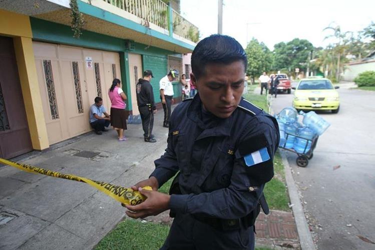Un policía cierra el paso en el lugar donde quedó el cadáver del trabajador, a un costado de los garrafones de agua que vendía. (Foto Prensa Libre: Érick Ávila)