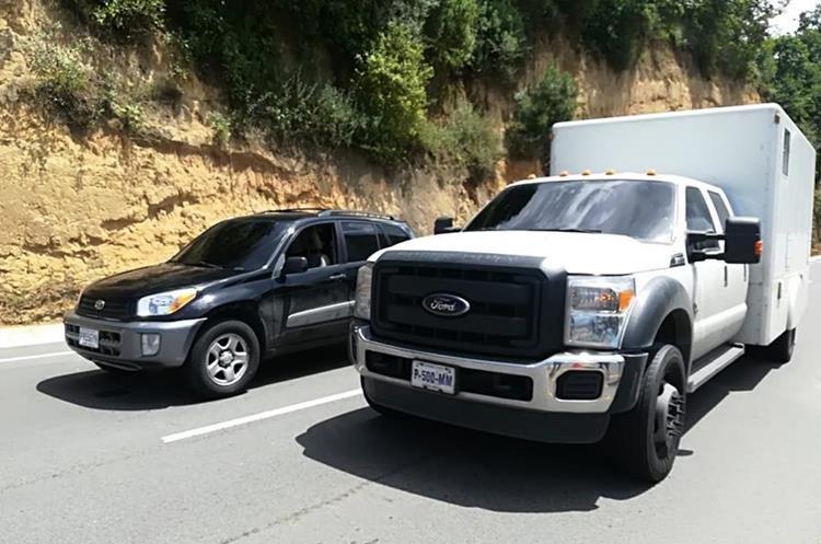 La Policía utilizó un escáner -vehículo blanco- para revisar la estructura de la camioneta donde se sospechó lleva droga. (Foto Prensa Libre: PNC)