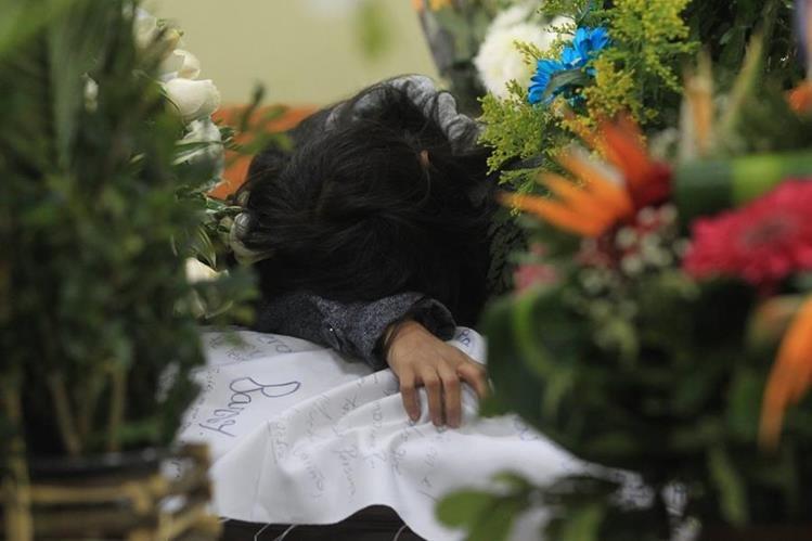 Una familiar de Nimcy Marroquín llora sobre el féretro, que fue cubierto con una manta firmada por todos sus amigos del colegio. (Foto Prensa Libre: Estuardo Paredes)