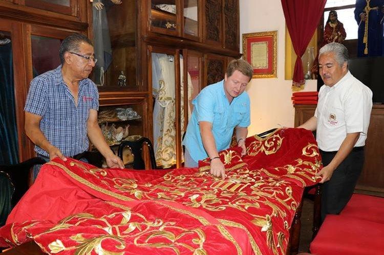 Integrantes de la Hermandad de La Merced muestran la túnica que vestirá la imagen de Jesús Nazareno. (Foto Prensa Libre: Julio Sicán)