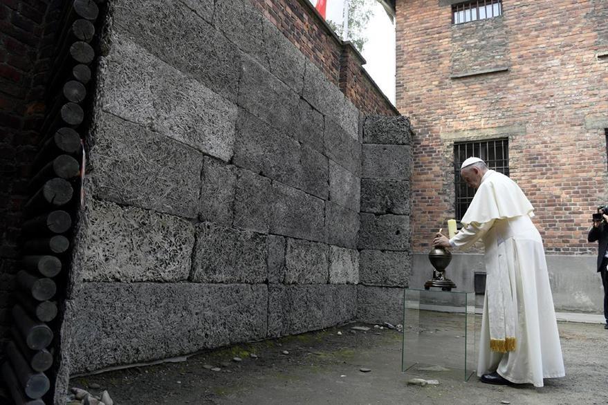 El papa Francisco ora frente el paredón donde millones fueron fusilados en Auschwitz, Polonia. (Foto Prensa Libre: AP).
