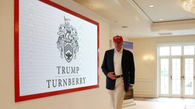 Trump camina junto a una imagen de su nuevo escudo en el Turnberry gold resort en Escocia. REUTERS