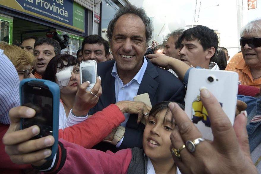El oficialista Daniel Scioli acepta tomarse una fotografía con simpatizantes. (Foto Prensa Libre: AFP).