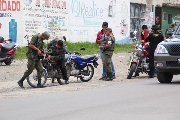 <p>Soldados y agentes de la PNC solicitan documentos a pilotos de motocicletas, en una calle de la cabecera de Huehuetenango. (Foto Prensa Libre: Mike Castillo) <br></p>