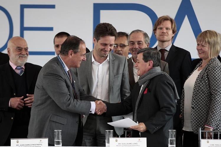 Representantes del Gobierno de Colombia (a la izq.) y delegados del ELN se saludan en Quito, Ecuador. (Foto Prensa Libre: EFE).