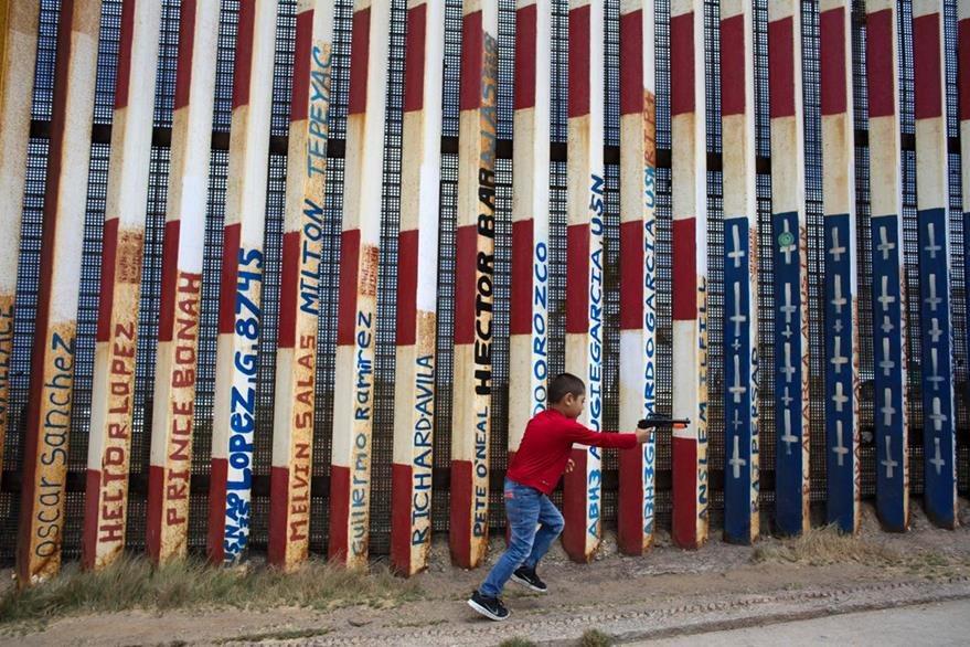 Un niño juega a un costado del muro en el lado mexicano. (Foto Prensa Libre: AFP).