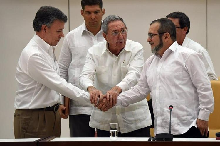 Raúl Castro (centro) propició un apretón de manos entre Santos y Timochenko.(Foto Prensa Libre: AFP).