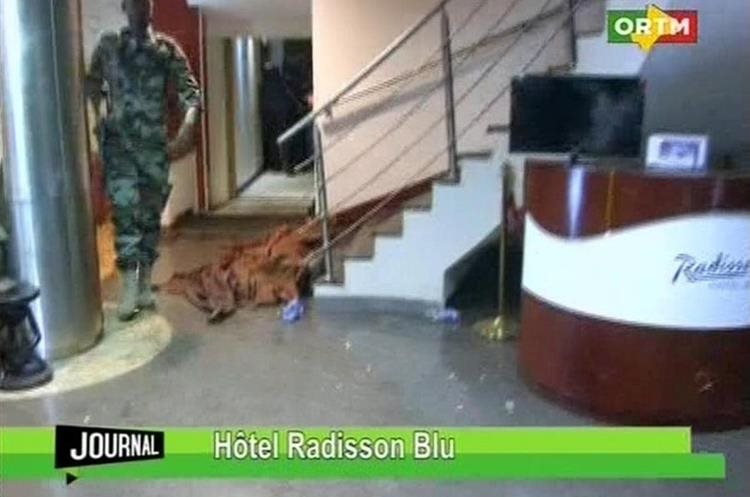 "In this TV image taken from Mali TV ORTM, a member of the security forces walks past a body lying covered on the floor in the Radisson Blu Hotel  hotel in Bamako, Mali, Friday Nov. 20, 2015.  Men shouting ""God is great"" and armed with guns and throwing grenades stormed into the Radisson Blu Hotel in Mali"