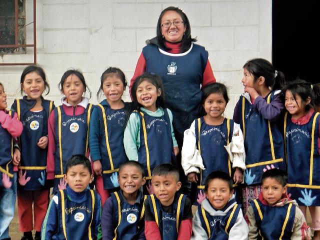 Sonia Menchú, junto a una de sus promociones de preprimaria, en la escuela rural de Totonicapán donde trabaja desde hace 11 años. (Foto Prensa Libre: María José Longo)