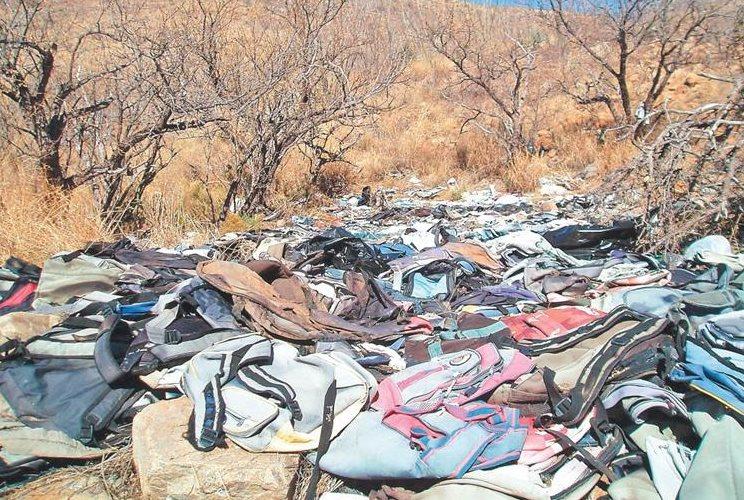Decenas de mochilas abandonadas en el desierto. (Foto: La Prensa Gráfica).