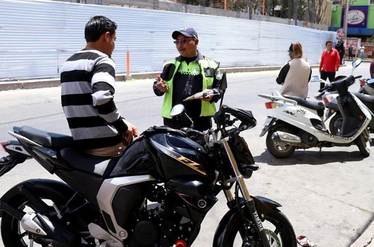 Agente de PMT de Huehuetenango explica los motivos por los que emite multa a un motorista durante un operativo en la cabecera. (Foto Prensa Libre: Mike Castillo)