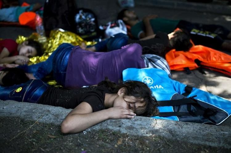 """A young migrant sleeps on the ground with other migrants in a park on the Kos island in Greece, on August 10 , 2015. The United Nations warned on August 7 that migrants landing in Greece were facing """"shameful"""" conditions, with the crisis-hit country claiming it was unable to cope with the massive influx on its Aegean islands. Some 124,000 people, almost all of them fleeing war and persecution in Syria, Afghanistan and Iraq, have come ashore since the beginning of the year -- a 750-percent increase from the same period last year. AFP PHOTO / ANGELOS TZORTZINIS"""