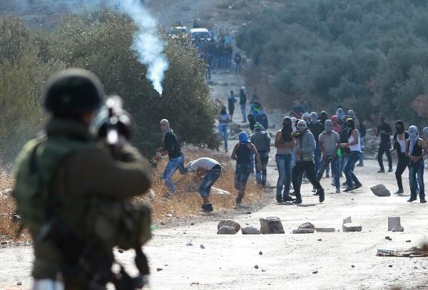 Un soldado israelí dispara contra palestinos durenta el enfrentamiento.