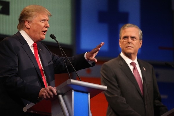 Donald Trump, izquierda, habla con Jeb Bush como escucha. (Foto Prensa Libre: AP)