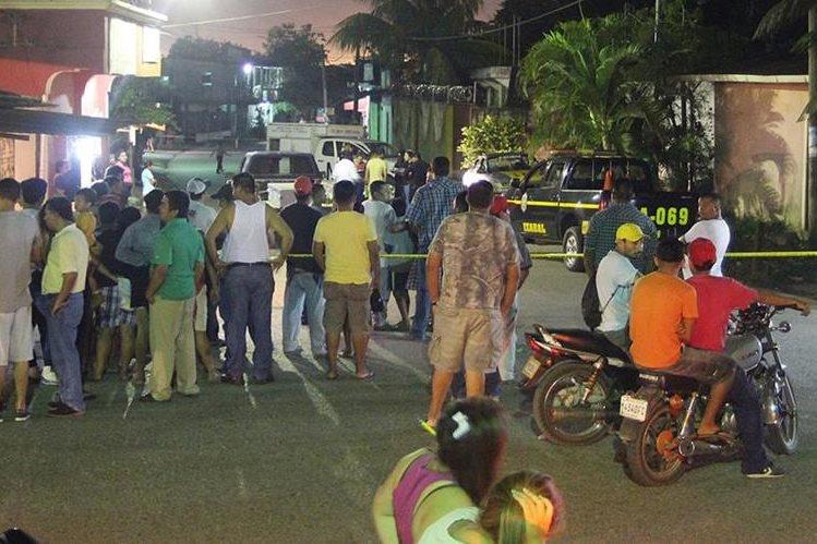 Vecinos de Santo Tomás de Castilla, Puerto Barrios, Izabal, se reúnen donde murió baleado un taxista. (Foto Prensa Libre: Dony Stewart)
