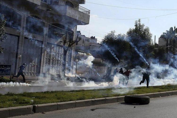 Manifestantes palestinos corren para protegerse de los gases lacrimógenos lanzados por soldados israelíes en el conflicto que cada día se recrudece más. (Foto Prensa Libre: EFE).