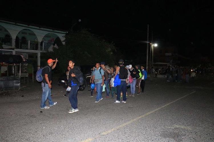 Salvadoreños que no cuentan con dinero para pagar un pasaje de bus continúan su trayecto a pie con la esperanza de que guatemaltecos les apoyen con transporte hacia Escuintla. (Foto Prensa Libre: Enrique Paredes)
