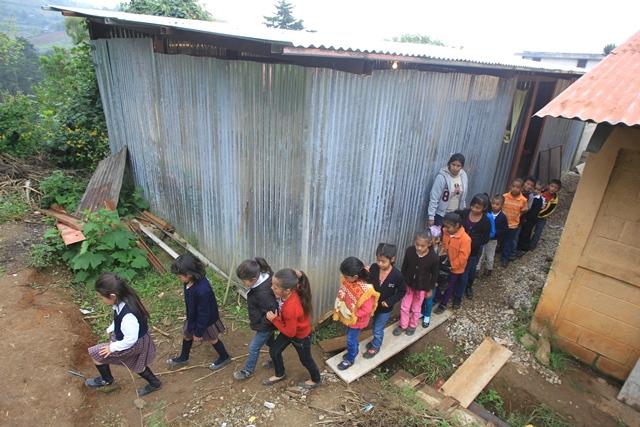 Estudiantes salen de un aula construida con láminas y madera. (Foto Prensa Libre: Esbin García)