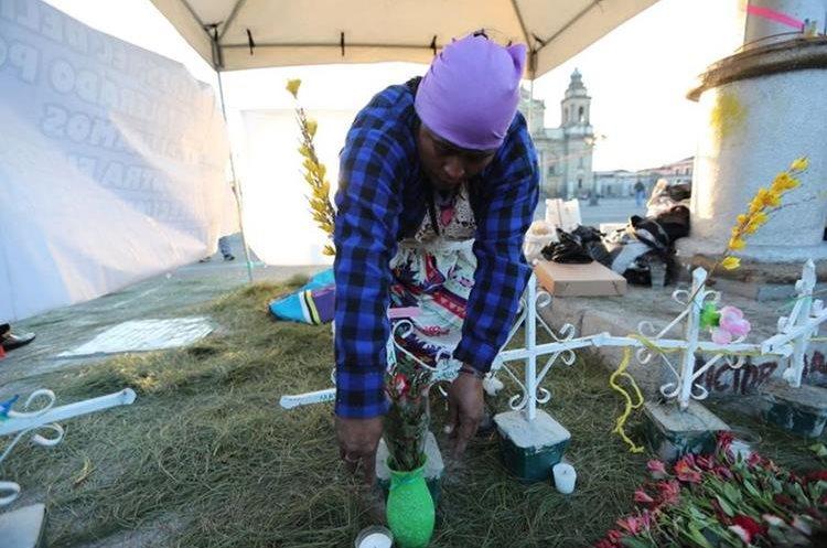 Carmen Urías, madre de una de las víctimas, acomoda las cruces blancas que recuerdan el nombre de las niñas. (Foto Prensa Libre: Érick Ávila)