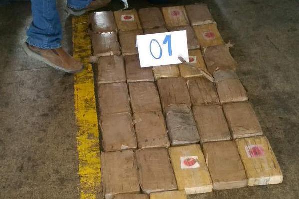 Paquetes con posible droga son contabilizados por investigadores de la PNC en Portuaria Santo Tomás de Castilla, Puerto Barrios, Izabal. (Foto Prensa Libre: PNC)