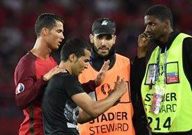 Cristiano le pidió a los guardias de seguridad que esperaran para que el aficionado se tomará la fotografía. (Foto Prensa Libre: AFP)