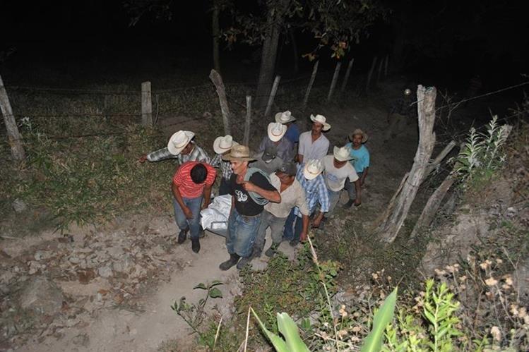 Un grupo de vecinos traslada el cadáver de una de las dos víctimas. (Foto Prensa Libre: Mario Morales).