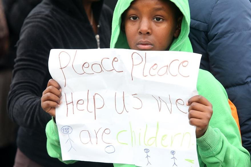 """Una niña sostiene un cartel en donde se lee: """"porfavor, porfavor, ayúdanos, somo niños"""". (Foto Prensa Libre: AFP)."""