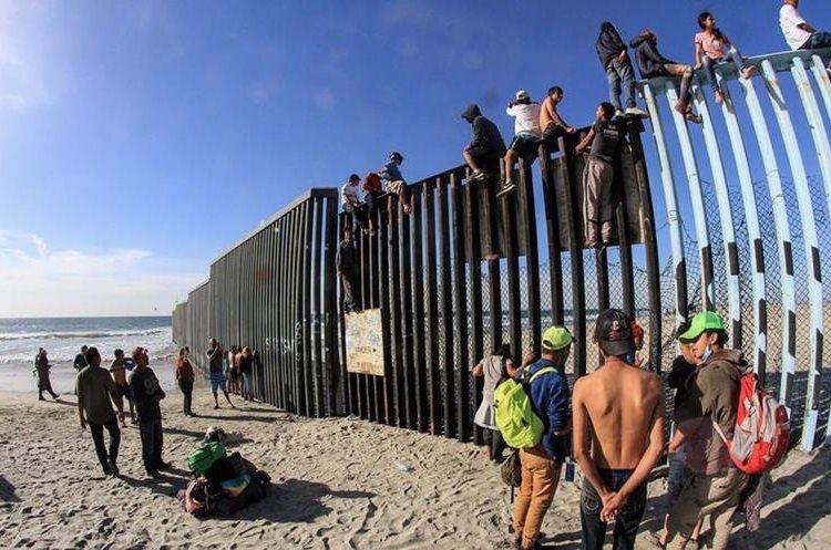 Integrantes de la caravana de centroamericanos escalan el muro fronterizo en Tijuana.