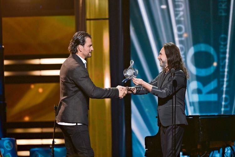 Marco Antonio Solís le entregó el galardón a Ricardo Arjona. (Foto Prensa Libre: AFP)