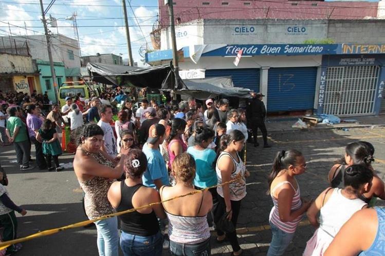 Comerciantes y compradores observan la escena del doble crimen. (Foto Prensa Libre: Erick Ávila)