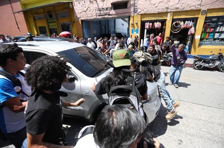Uno de los manifestantes se subió al bumper del vehículo para evitar que el ministro de Salud huyera del lugar. (Foto Prensa Libre: Esbin García)