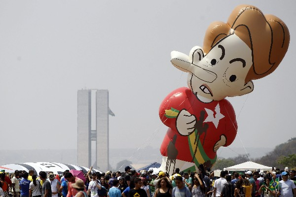 <em>Muñeco gigante de la presidenta Dilma Rousseff es ubicado por protestantes cerca del desfile militar.</em>