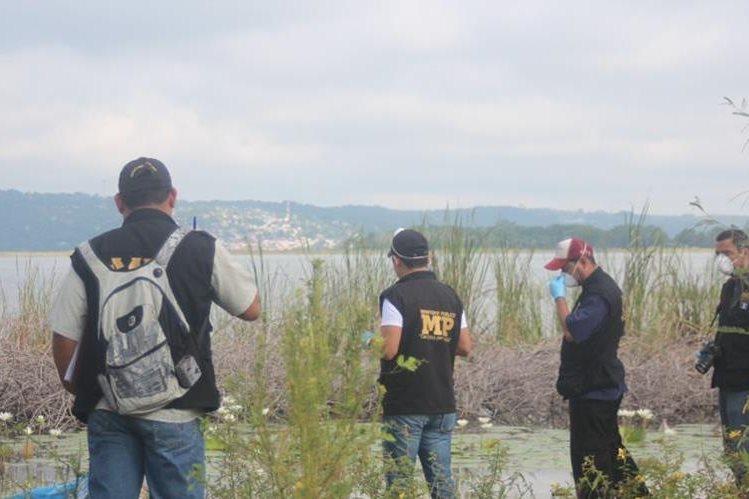 Investigadores reúnen evidencias en el lugar del hallazgo del cadáver. (Foto Prensa Libre: Rigoberto Escobar).