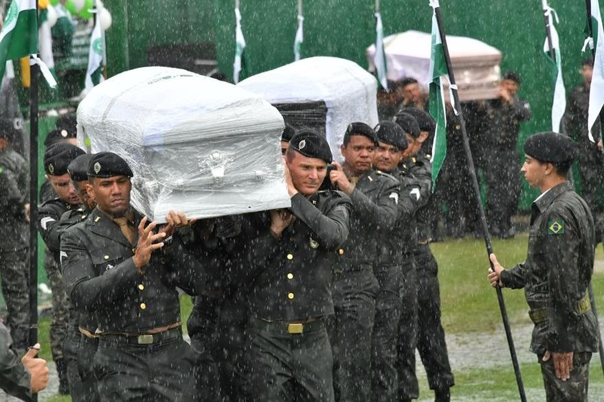 Soldiers carry into the stadium under heavy rain the coffins of the members of the Chapecoense Real football club team killed in a plane crash in Colombia, in  Chapeco, Santa Catarina, southern Brazil, on December 3, 2016.  The bodies of 50 players, coaches and staff from a Brazilian football team tragically wiped out in a plane crash in Colombia arrived home Saturday for a massive funeral. / AFP PHOTO / Nelson Almeida