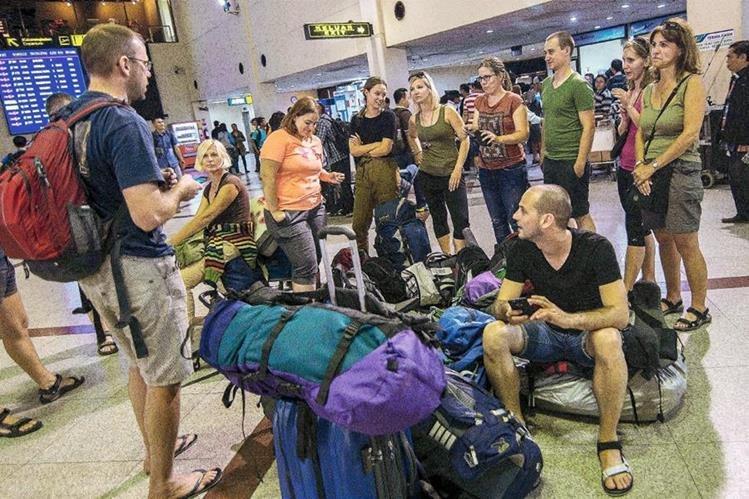 Pasajeros esperan en el aeropuerto de Juanda, cerca de Surabaya ubicada en el este de la isla de Java. (Foto Prensa Libre: AFP).
