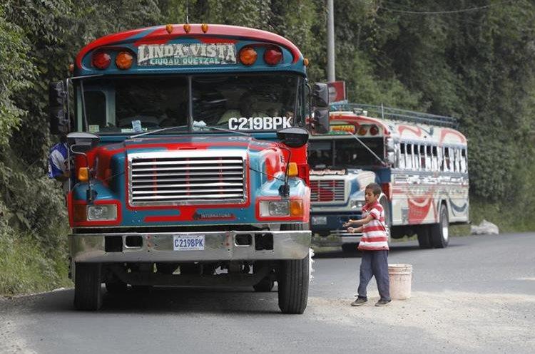 Luis Alexis Guzmán, de 8 años de edad, acarrea tierra con una cubeta para rellenar los agujeros del asfalto y espera que los pilotos le den un quetzal por su trabajo. bajada del Milagro, ruta a ciudad Quetzal.   Fotografía: Paulo Raquec