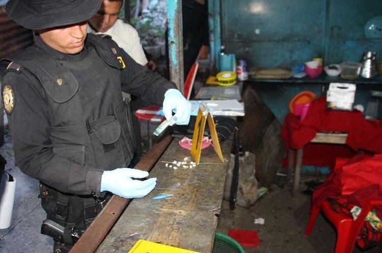 Agente de la PNC realiza prueba con reactivos para confirmar que se trataba de cocaína. (Foto Prensa Libre: PNC)