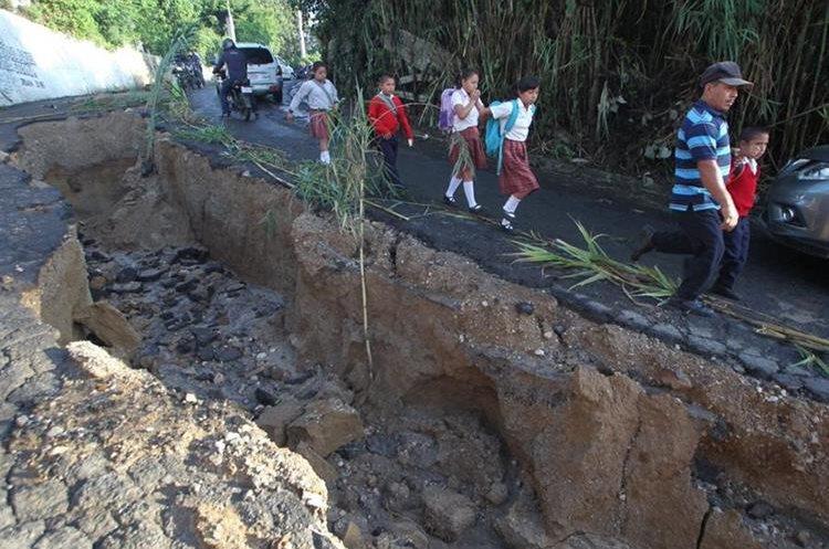 Estudiantes pasan a un costado del hundimiento en la ruta entre La Comunidad y Las Charcas, zona 10 de Mixco, (Foto Prensa Libre: Érick Ávila)