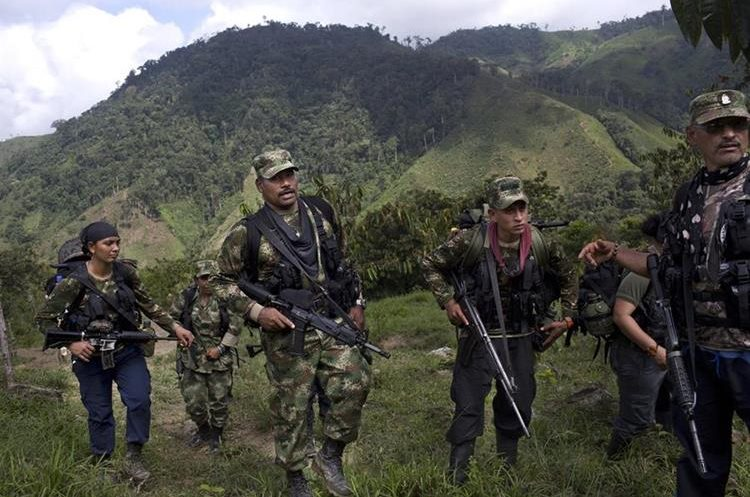 In this Jan. 6, 2016 photo, Juan Pablo, center, a commander of the 36th Front of the Revolutionary Armed Forces of Colombia, or FARC, walks with his comrades in Antioquia state, in the northwest Andes of Colombia. As a commander of the 36th Front, one of the most militarily-active in a half century of warfare, the 41-year-old is capable of reciting verbatim passages from Fidel Castro