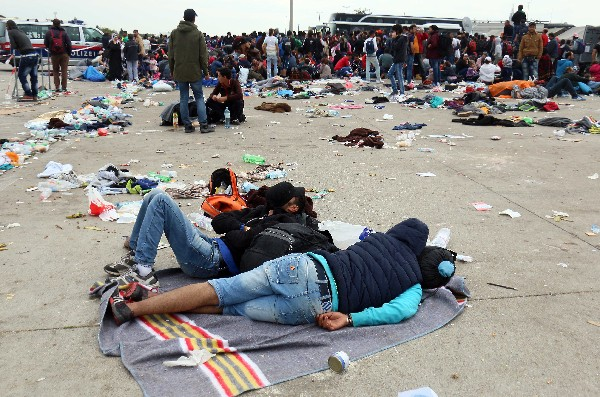 Refugiados toman un descanso a su llegada a la frontera entre Austria y Hungría.