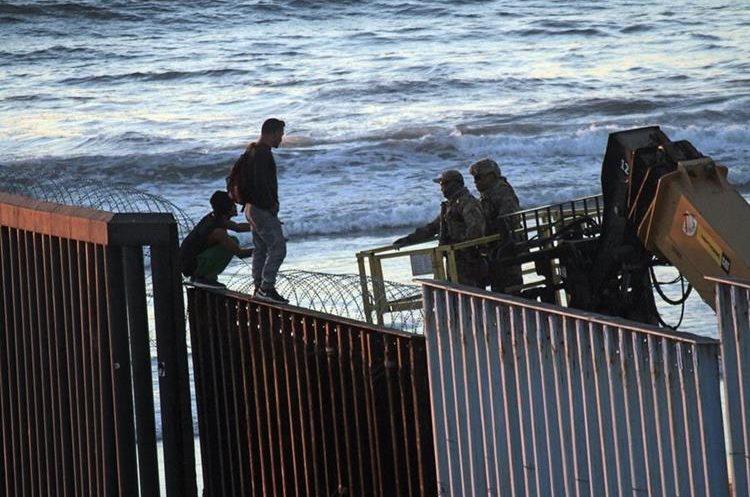 Migrantes centroamericanos observan a dos soldados del ejército de Estados Undios, en Tijuana.
